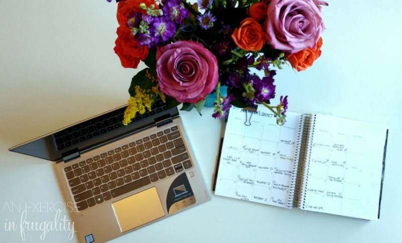 white desk with laptop, flowers and planner