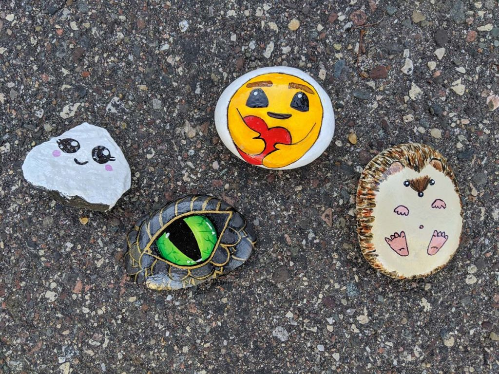 four painted rocks on a blacktop driveway.