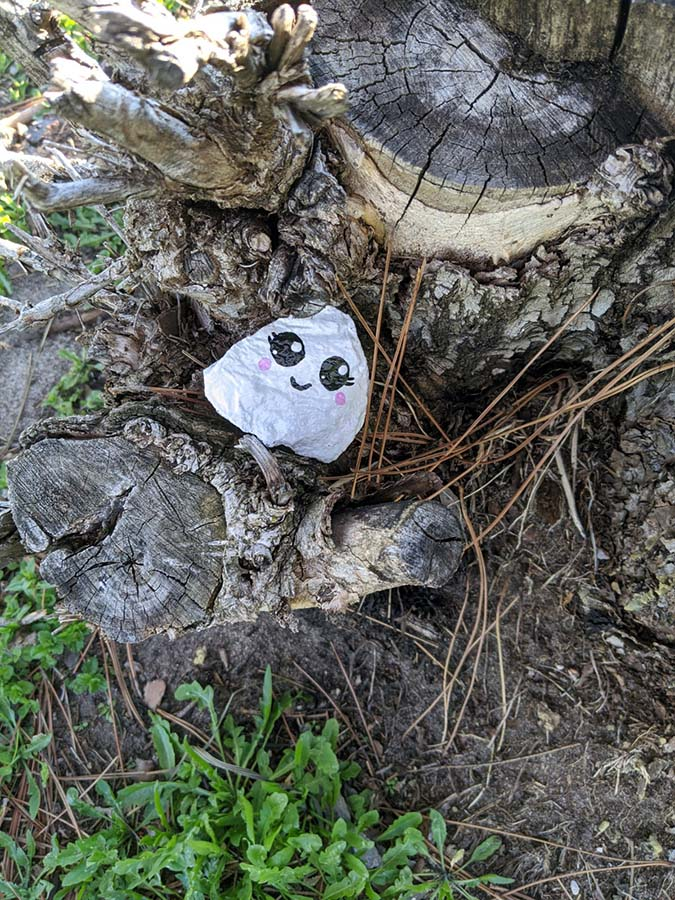 small painted rock with kawaii ghost face on a tree stump