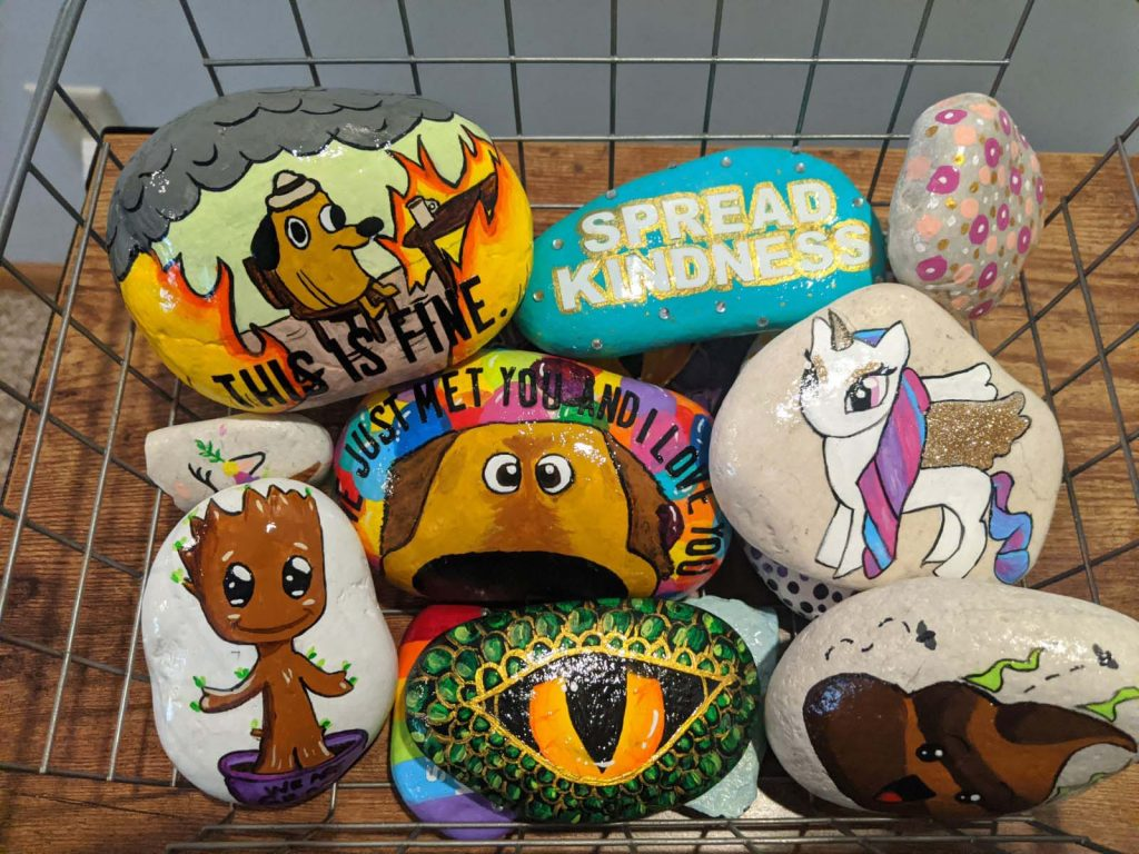 basket full of colorful painted rocks with various characters