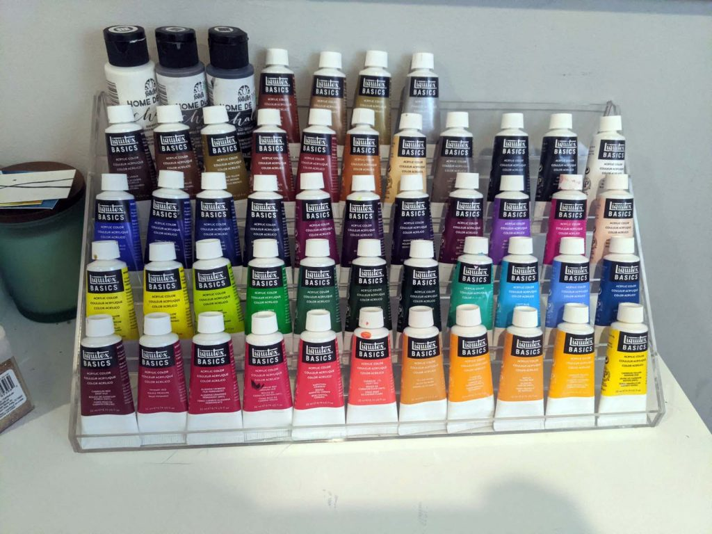 display case with a rainbow of paint colors