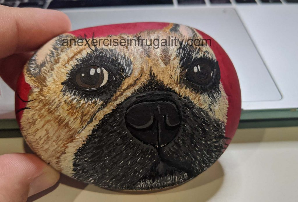 painted rock with a french bulldog face and red background