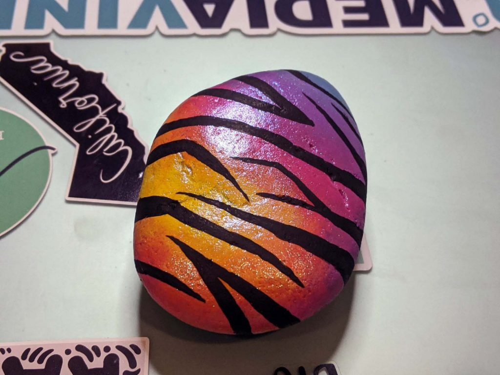 multi-color painted rock with zebra stripes and glitter
