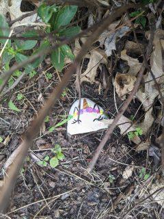 unicorn painted rock hiding in a bush